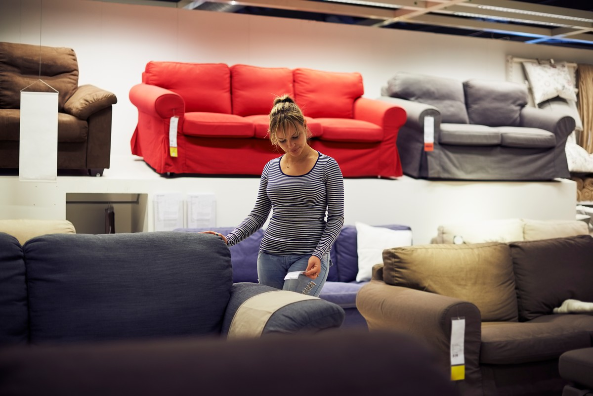 young-hispanic-woman-shopping-for-furniture-sofa-and-home-decor-in-store